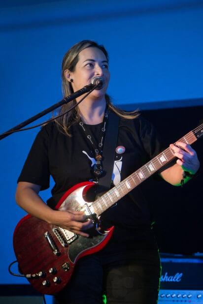 Colaboradora cantando e tocando guitarra em evento da empresa.
