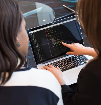 Colaboradoras olhando para o código em notebook.