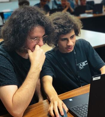 Colaboradores olhando para a tela de um notebook.