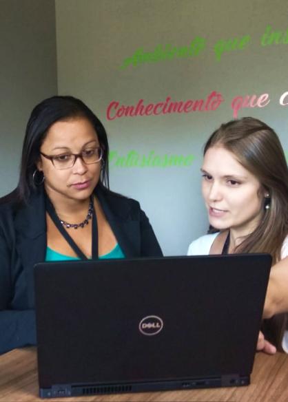 Colaboradoras conversando e olhando para a tela de um notebook.