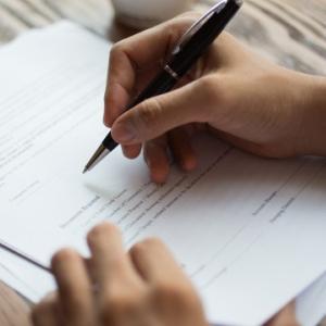 Pessoa escrevendo de caneta em um papel.
