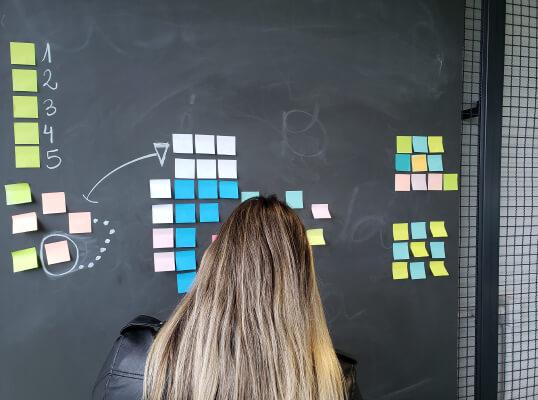 Colaborador desenhando processos em uma parede de vidro.