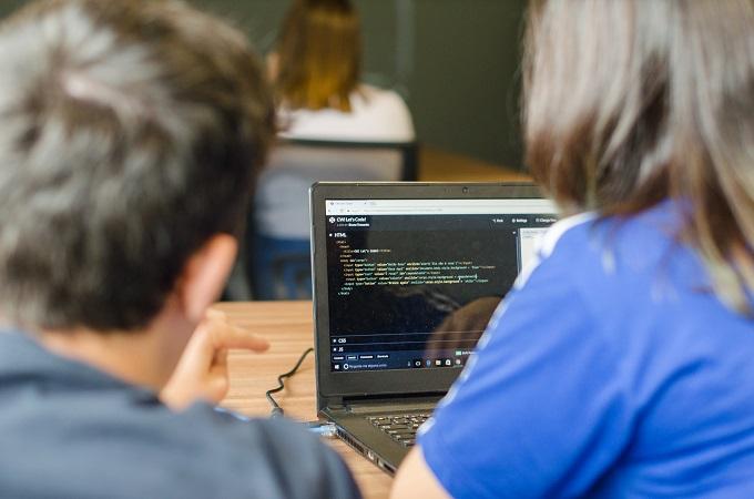 Homem mostrando código HTML a estudante de programação.