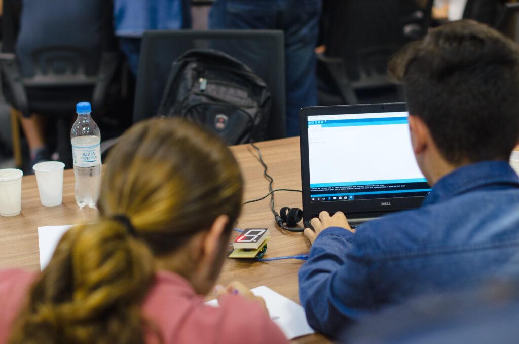 Estudantes resolvendo desafio de programação com Arduino.