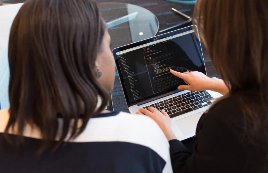 Mulheres de costas falando sobre um código-fonte na tela de um notebook.