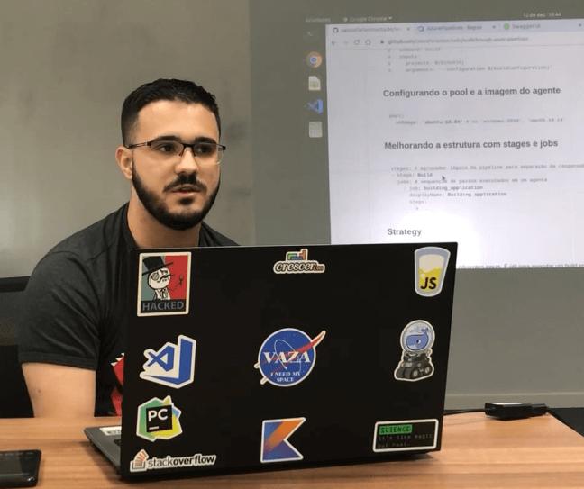 Homem em frente a um notebook dando aula de programação com projeção de tela ao fundo.