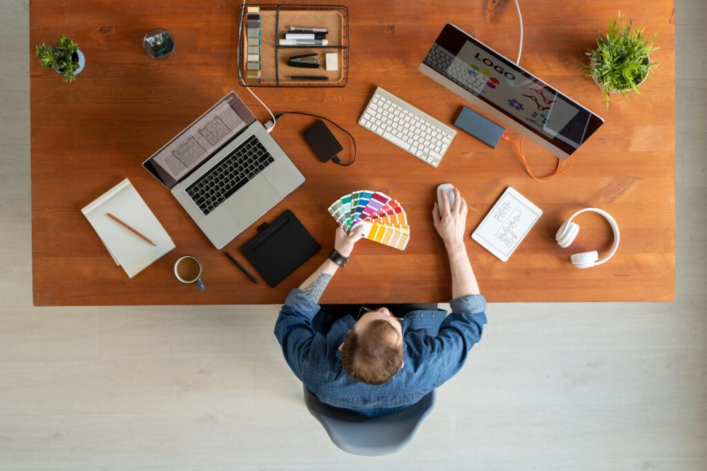 Imagem com perspectiva de cima de um homem branco sentado em uma mesa mexendo em um computador. Percebemos alguns blocos de anotações, um fone de ouvido e uma paleta de cores espalhadas na mesa.